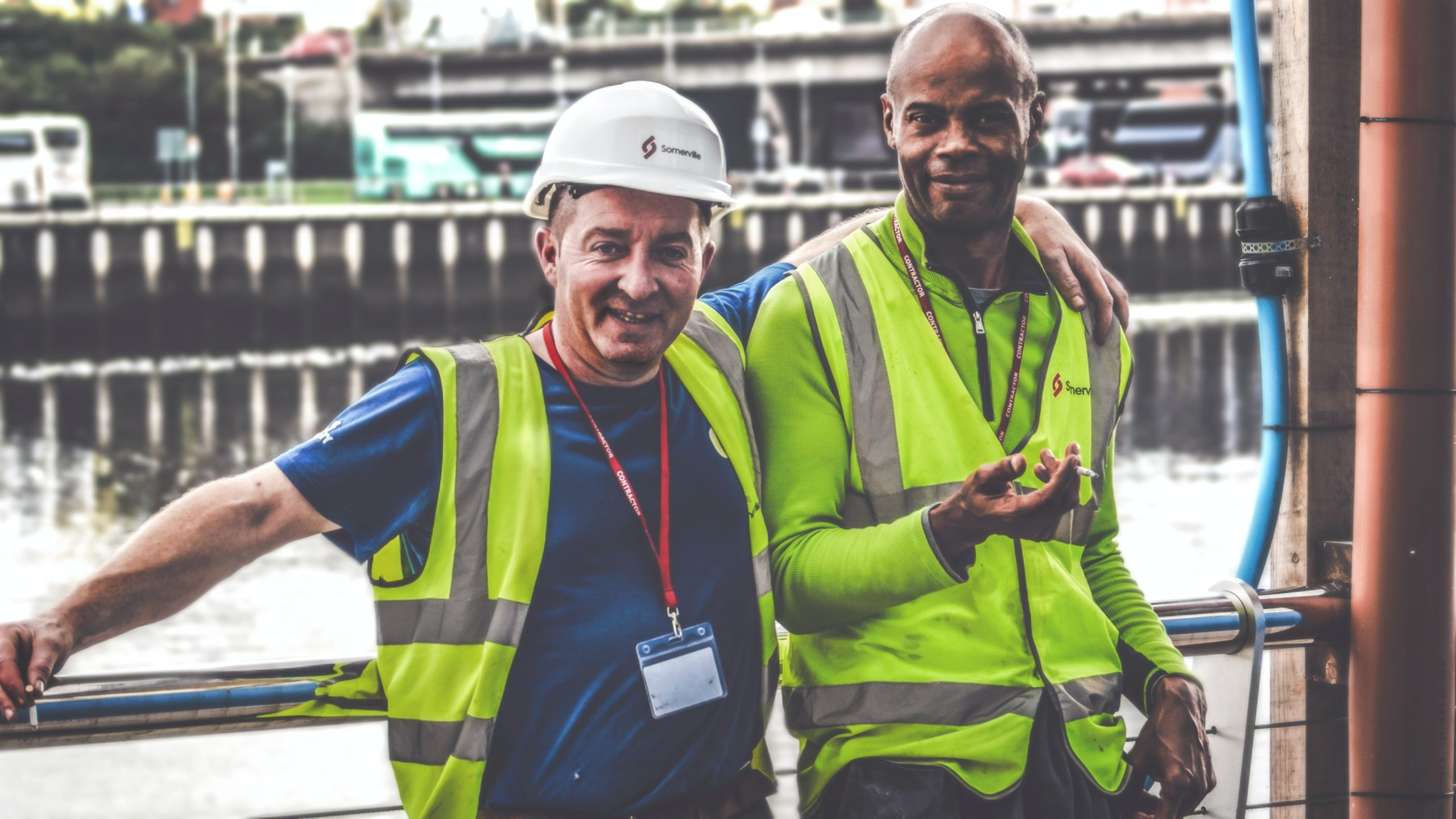 selective focus photography of two men standing side by side wearing green reflective vests